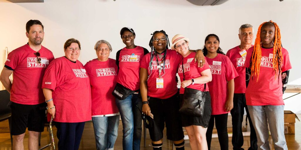 Word On The Street festival volunteers in pink t-shirts smile for the camera at our 2019 festival.